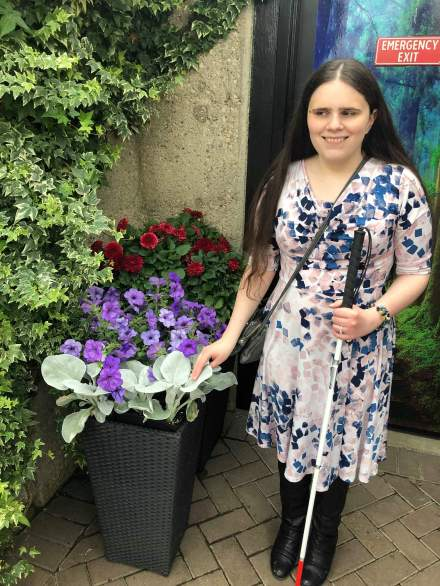 Meagan, wearing a colourful summer dress and tall black boots, smiles as she touches soft, fuzzy leaves. Purple petunias are visible in the background.