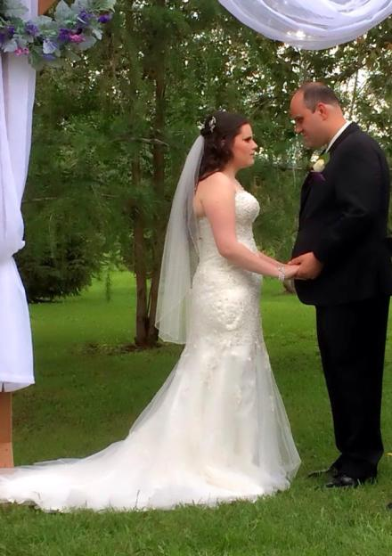 Meagan and her husband face each other, smiling and holding hands. She wears an ivory mermaid-style wedding gown covered with seed pearls. A veil is pinned over her hair. He wears a black tuxedo. A wooden archway, decorated with flowers, is in the background.